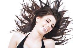Lachende sorglose Frau L, die ihr Haar wirft Stockbild