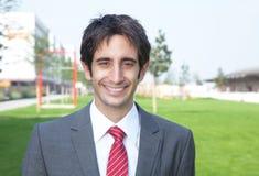 Lachende Spaanse zakenman buiten in een park Stock Foto