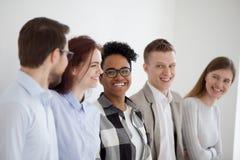 Lachende Stellung des glücklichen gemischtrassigen Teams nahe Bürowand stockfotos