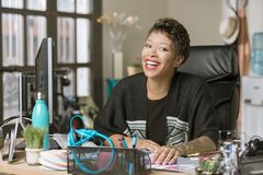 Lachende stilvolle Frau in einem kreativen Büro lizenzfreie stockbilder