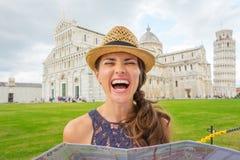 Lachende touristische haltene Karte der Frau im nahen lehnenden Turm von Pisa lizenzfreie stockfotos
