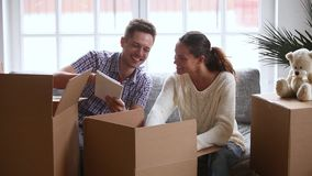 Lachende Unterhaltung der glücklichen jungen Paare, offene Pappschachteln zusammen auspackend stock video footage