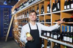 Lachende verkopersmens die fles wijn bevorderen Stock Afbeeldingen