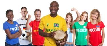 Lachende voetbalverdediger met trommel en ventilators van ander land stock afbeeldingen
