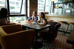 Lachende vrienden die bij restaurant zitten en met koppen van koffie spreken Royalty-vrije Stock Foto's