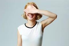 Lachende vrouw die haar ogen met hand sluiten stock fotografie
