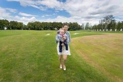 Lachende vrouw die vrolijke babyjongen en het hebben van pret op gras houden Royalty-vrije Stock Afbeeldingen