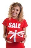 Lachende vrouw met blond haar en gift in een verkoop-overhemd stock afbeelding