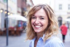 Lachende vrouw met krullend blond haar in de stad Royalty-vrije Stock Afbeeldingen