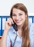 Lachende vrouw met lang blond haar op kantoor die bij telefoon spreken stock afbeelding