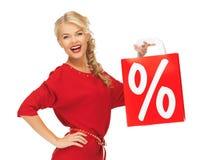 Lachende vrouw in rode kleding met het winkelen zak Stock Afbeelding