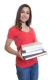 Lachende vrouwelijke student die met lang donker haar en boeken kijken royalty-vrije stock foto's