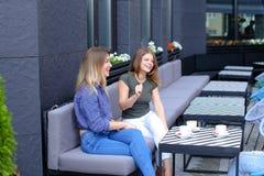 Lachende vrouwen die bij koffie dichtbij koppen van koffie op lijst zitten Royalty-vrije Stock Foto's