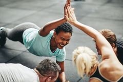 Lachende vrouwen die hoog terwijl het planking in een gymnastiekklasse fiving royalty-vrije stock foto's