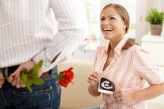 Lachende zwangere vrouw die bloemen krijgt Stock Afbeelding