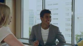 Lachende zwarte mens met collega's in bureau stock footage
