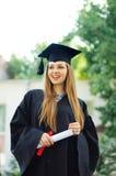 Lachender Absolvent mit einem Diplom Stockbild