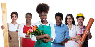 Lachender afrikanischer Florist mit Gruppe anderer internationaler Lehrlinge stockfotos