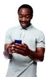 Lachender afrikanischer Mann, der Smartphone verwendet Lizenzfreie Stockbilder