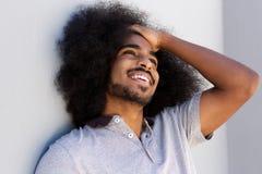 Lachender Afromann mit der Hand im Haar, das weg schaut Lizenzfreies Stockfoto