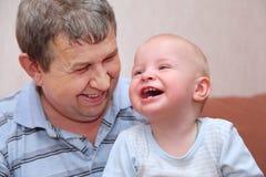 Lachender alter Mann und sein Enkel Stockfotos