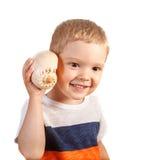 Lachender blonder Junge, der auf Muschel hört Lizenzfreie Stockfotografie