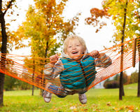 Lachender blonder Junge legt auf Netz der Hängematte im Park Lizenzfreie Stockfotos