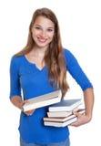 Lachender blonder Student, der ein Buch empfiehlt Lizenzfreie Stockfotos