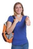 Lachender blonder Student mit dem Rucksack, der sich Daumen zeigt Stockfoto