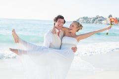 Lachender Bräutigam, der seine recht blonde Frau trägt Stockbild