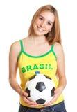 Lachender brasilianischer Sportfan mit Ball Stockfotografie