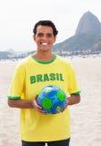 Lachender brasilianischer Sportfan mit Ball bei Rio de Janeiro Stockfotografie