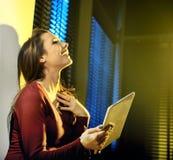 Lachender Brunette, der eine Tablette verwendet lizenzfreie stockfotos
