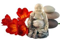 Lachender Buddha, rote Taglilien Steine. Stockfotos