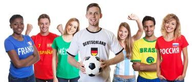 Lachender deutscher Fußballfan mit zujubelnder Gruppe anderer Fans Lizenzfreies Stockbild