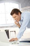 Lachender Fachmann beim Überlandleitungaufruf mit Laptop Lizenzfreies Stockfoto