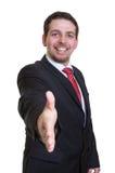 Lachender Geschäftsmann im schwarzen Anzug, der Hand für Händedruck erreicht Stockfoto