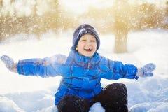 Lachender glücklicher Junge, sitzend im Schneepark Lizenzfreie Stockfotografie