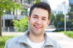 Lachender hispanischer Kerl in einer grauen Jacke draußen Stockfotos