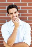 Lachender hispanischer Kerl vor einer Backsteinmauer Lizenzfreies Stockbild