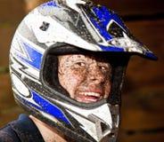 Lachender jugendlich Junge mit schmutzigem Gesicht, nachdem er eine vierfache Leitung angetrieben hat, fahren rad Stockfotografie