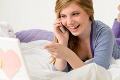 Lachender Jugendlicher, der durch das Sprechen am Telefon sich entspannt Stockbilder