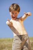 Lachender Junge, der oben Daumen aufwirft Lizenzfreies Stockfoto