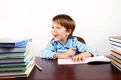Lachender Junge, der am Schreibtisch mit vielen Büchern sitzt Stockbilder