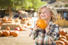 Lachender Junge, der seinen Kürbis an einem Kürbis-Flecken hält Lizenzfreies Stockfoto