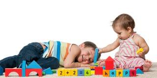 Lachender Junge und ein Baby spielen Lizenzfreie Stockfotografie