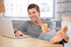 Lachender junger Mann, der zu Hause Computer verwendet Lizenzfreie Stockfotografie