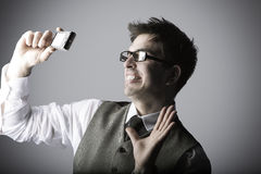 Lachender junger Mann macht ein selfie mit einer Kompaktkamera Stockfoto