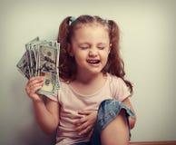 Lachender junger Sieger, der Dollar mit geschlossenem Auge hält des Kindes III Stockfotos