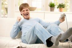 Lachender Kerl mit Computerspiel Stockfotografie